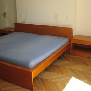 Kirschbaum Bett. Das Kopfteil ist 90 cm hoch, die Seitenteile 8 cm breit. In den Nachtkästen ist ein Schub integriert.